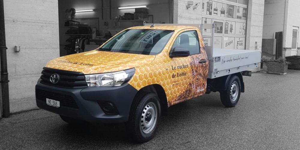 Pose d'un sticker sur une voiture pour l'entreprise Le rucher de Leitiz